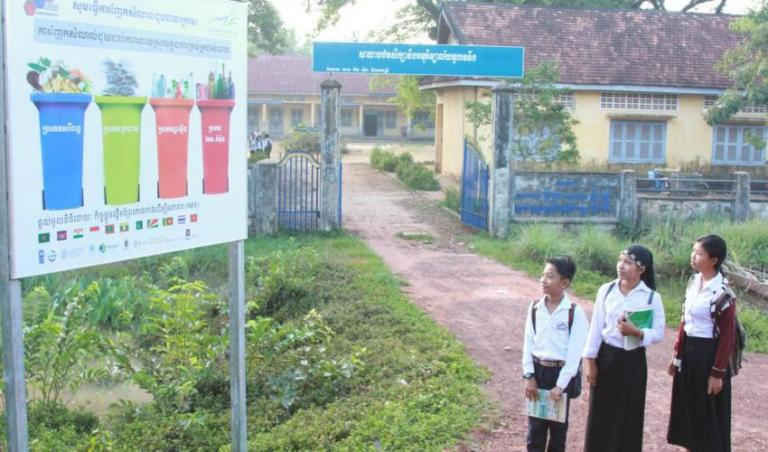 Bảng quảng cáo về quản lý chất thải phù hợp được lắp đặt trước trường trung học ở xã Toul Toueng, Campuchia