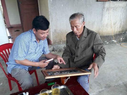 Ông Phạm Xuân Liên nâng niu, tự hào về bức ảnh ông được gặp Bác Hồ.