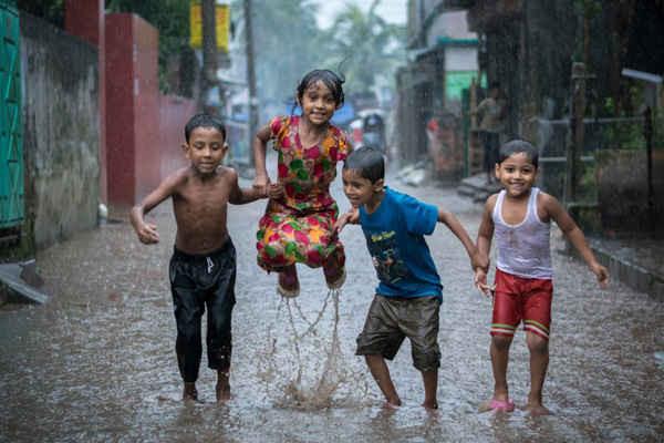 """Hình ảnh với tựa đề Happiness on a Rainy Day (tạm dịch """"Hạnh phúc vào một ngày mưa"""") của Fardin Oyan, người Bangladesh. Đây là nhiếp ảnh gia môi trường trẻ của năm nay. Qua bức ảnh, độc giả có thể thấy rõ nhiều trẻ em ở Bangladesh thích tắm và chơi trong mưa. Đất nước Bangladesh bằng phẳng và bị chiếm đóng bởi đồng bằng sông Hằng-Brahmaputra khổng lồ thường phải hứng chịu các trận lũ lụt, đặc biệt trong mùa mưa"""