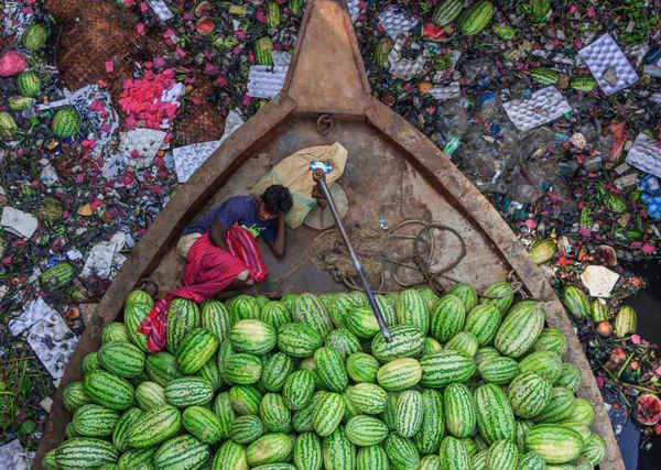 """Floating Life on River Under Pollution (tạm dịch """"Cuộc sống trôi nổi trên dòng sông ô nhiễm"""") của Tapan Karmaker, nhiếp ảnh gia môi trường nhận được nhiều lời khen ngợi trong năm nay. Một người bán dưa hấu nằm trên thuyền của mình trong khi con thuyền trôi dạt trên dòng sông Burigongga bị ô nhiễm nặng nề ở Dhaka, Bangladesh. Ảnh: Tapan Karmaker"""