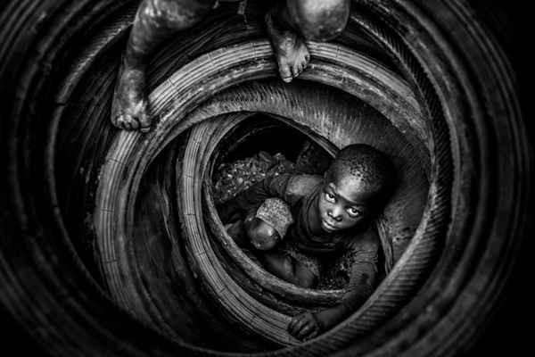 """""""Boulmigou: The Paradise of Forgotten Hearts"""" của Antonio Aragón Renuncio – nhiếp ảnh gia được yêu thích trong năm. Trong bức ảnh này, trẻ em chơi với lốp xe cũ trong khi những lốp xe này có thể sẽ bị đốt cháy, làm nóng đá bên dưới và khiến đá dễ vỡ hơn trong mỏ đá Boulmigou bị ô nhiễm ở Ouagadougou, Burkina Faso. Hậu quả rất khủng khiếp: cháy, bệnh hô hấp, ô nhiễm nước ngầm và thậm chí gây tử vong"""