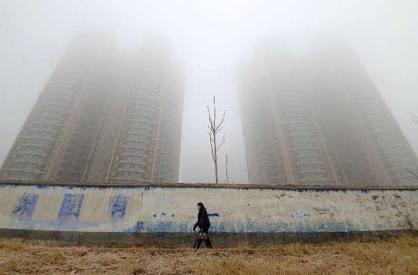 Một người phụ nữ đeo khẩu trang đi ngang qua các tòa nhà vào một ngày ô nhiễm ở Handan, tỉnh Hà Bắc, Trung Quốc vào ngày 12/1/2019. Ảnh: Reuters / Stringer