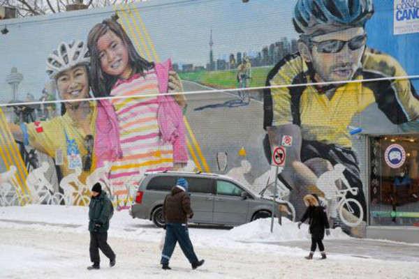 Mọi người đến nơi làm việc đi ngang qua một bức tranh tường bên ngoài một cửa hàng bán đồ thể thao trong cơn bão tuyết ở Toronto, Ontario, Canada vào ngày 12/2/2019. Ảnh: Reuters / Chris Helgren