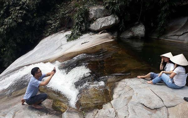 Du khách thích thú tạo dáng chụp ảnh bên dòng thác